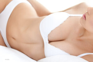 Mid Body Shot of WOman in Bed in White Bra and Underwear