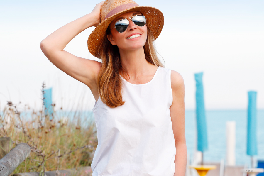 Woman Holding Hat on Head at the Beach