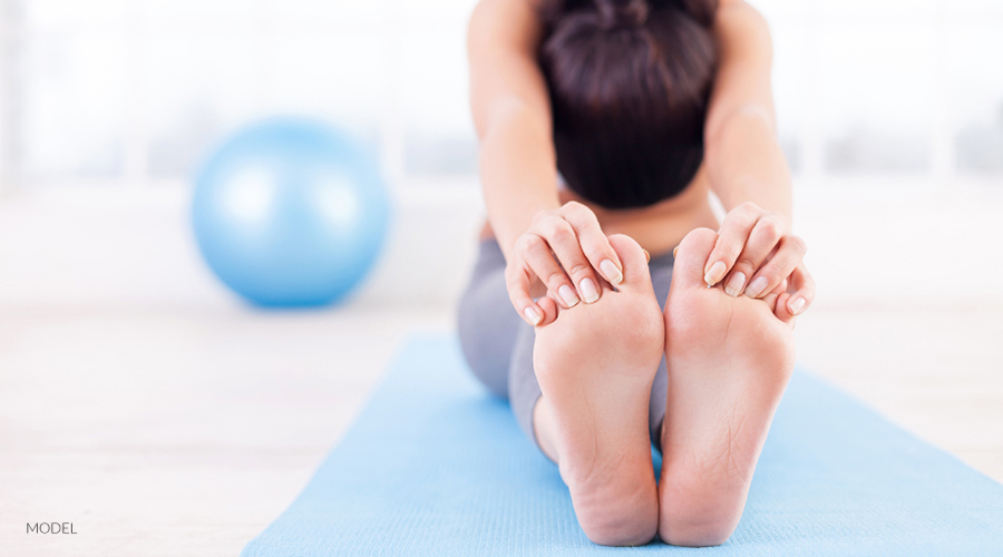Woman Stretching Legs on Yoga Mat
